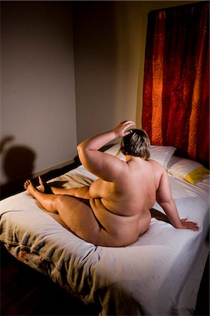 Overweight nude woman sitting on bed in bedroom, side view Stock Photo - Rights-Managed, Code: 842-02650273