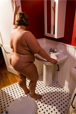 Overweight nude woman looking in bathroom mirror Stock Photo - Rights-Managed, Code: 842-02650283