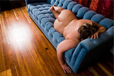 Overweight nude woman sitting on couch in living room, high angle view Stock Photo - Rights-Managed, Code: 842-02650294