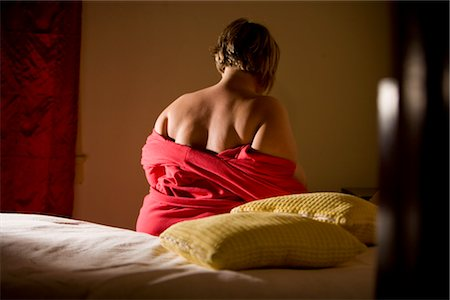 Overweight woman undressing from bathrobe in bedroom, rear view Stock Photo - Rights-Managed, Code: 842-02650299