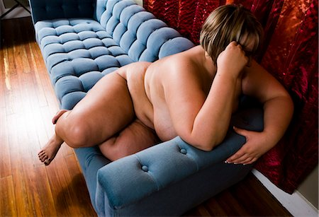 Overweight nude woman sitting on couch in living room, side view Stock Photo - Rights-Managed, Code: 842-02650292