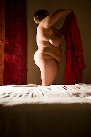 Overweight nude woman putting on bathrobe in bedroom, side view Stock Photo - Rights-Managed, Code: 842-02650304