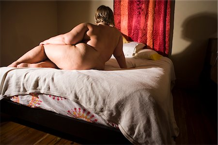 Overweight nude woman sitting on bed in bedroom, rear view Stock Photo - Rights-Managed, Code: 842-02650300