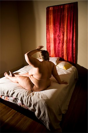 Overweight nude woman sitting on bed in bedroom, side view Stock Photo - Rights-Managed, Code: 842-02650301