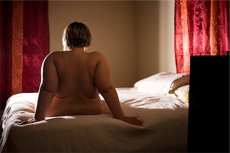 Overweight nude woman sitting on bed in bedroom, rear view Stock Photo - Rights-Managed, Code: 842-02650302