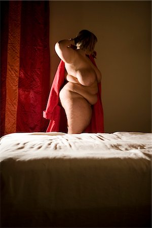 Overweight nude woman putting on bathrobe in bedroom, side view Stock Photo - Rights-Managed, Code: 842-02650303