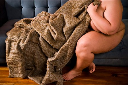Overweight nude woman sitting on couch with blanket, side view Stock Photo - Rights-Managed, Code: 842-02650316