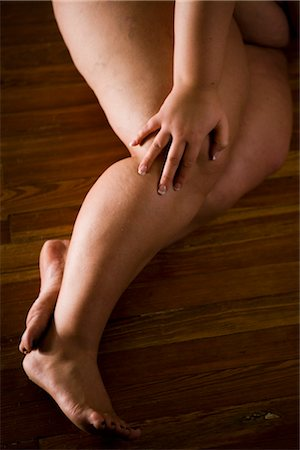 Overweight nude woman lying on hardwood floor, cropped view Stock Photo - Rights-Managed, Code: 842-02650318