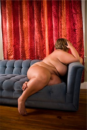 Overweight nude woman sitting on couch in living room, side view Stock Photo - Rights-Managed, Code: 842-02650311