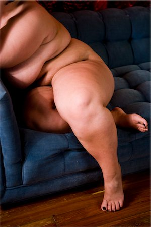 Overweight nude woman sitting on couch in living room, close-up Stock Photo - Rights-Managed, Code: 842-02650313