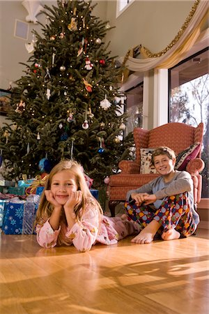Portrait of brother and sister on the floor next to Christmas tree and presents, looking at camera Stock Photo - Rights-Managed, Code: 842-02650322