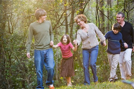 Portrait of family holding hands along edge of forest Stock Photo - Rights-Managed, Code: 842-02651525