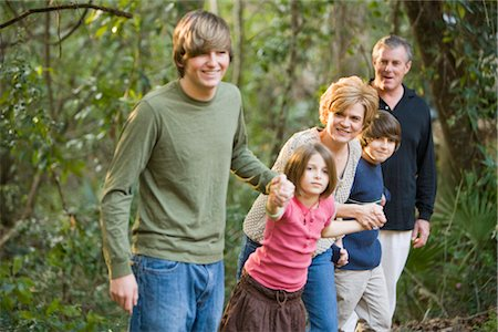 Portrait of family holding hands along edge of forest Stock Photo - Rights-Managed, Code: 842-02651550