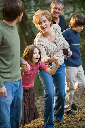 Portrait of family holding hands along edge of forest Stock Photo - Rights-Managed, Code: 842-02651551