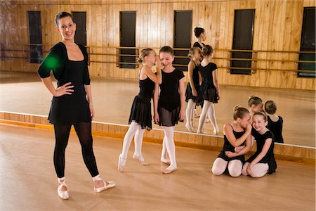 Portrait of ballet girls (8-9) whispering in ears while teacher smiling in foreground in dance studio Stock Photo - Rights-Managed, Code: 842-02652888