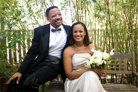Portrait of happy African American bride and groom sitting outside on bench on wedding day Stock Photo - Rights-Managed, Code: 842-02653404