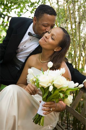 Happy African American groom sitting outside kissing his bride on wedding day Stock Photo - Rights-Managed, Code: 842-02653401