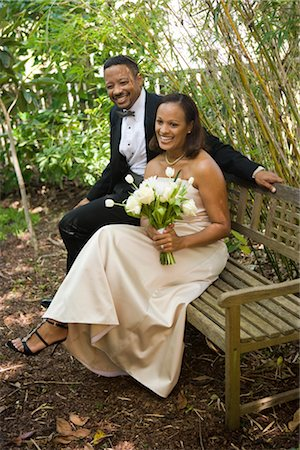 Happy African American bride and groom sitting outside on bench on wedding day Stock Photo - Rights-Managed, Code: 842-02653403