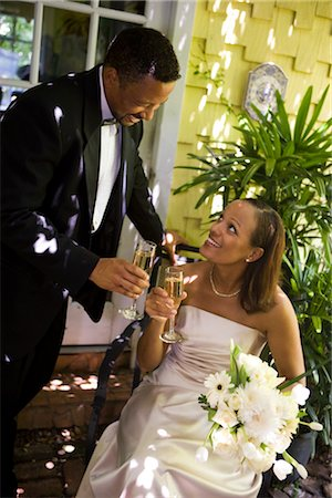 Happy African American bride and groom toasting champagne glasses outside on wedding day Stock Photo - Rights-Managed, Code: 842-02653410