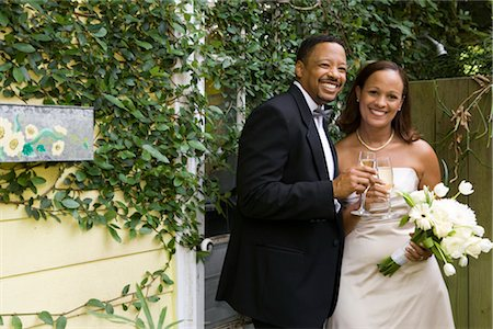 Portrait of happy African American bride and groom toasting champagne glasses outside on wedding day Stock Photo - Rights-Managed, Code: 842-02653412