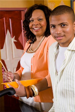 African American mother stirring a bowl in kitchen with teenage boy Stock Photo - Rights-Managed, Code: 842-02653449