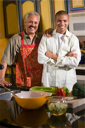 Portrait of African American father and teenage son standing in kitchen preparing meal, looking at camera Stock Photo - Rights-Managed, Code: 842-02653504