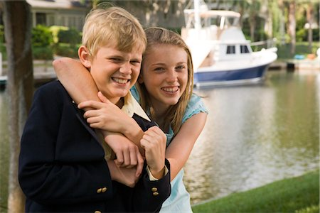 Closeup portrait of brother and sister hugging and smiling, with boat in background Stock Photo - Rights-Managed, Code: 842-02653548