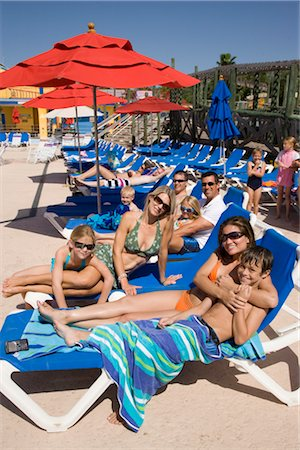 Friends and amily relaxing on deck chairs in water park Stock Photo - Rights-Managed, Code: 842-02653658