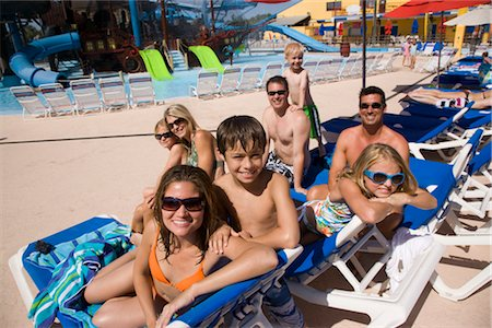 Friends and amily relaxing on deck chairs in water park Stock Photo - Rights-Managed, Code: 842-02653659