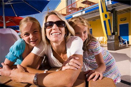 Closeup of young girls sitting with their mom at picnic table area of water park Stock Photo - Rights-Managed, Code: 842-02653707