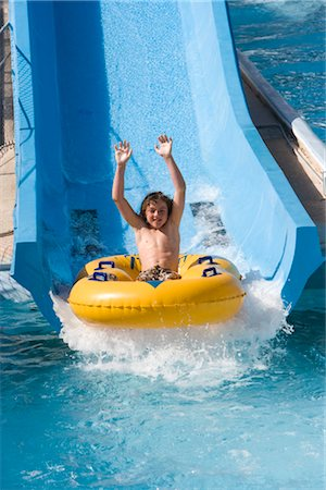Boy sliding down water slide on innertube in water park Stock Photo - Rights-Managed, Code: 842-02653748