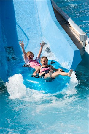 Girls sliding down water slide on innertube in water park Stock Photo - Rights-Managed, Code: 842-02653749
