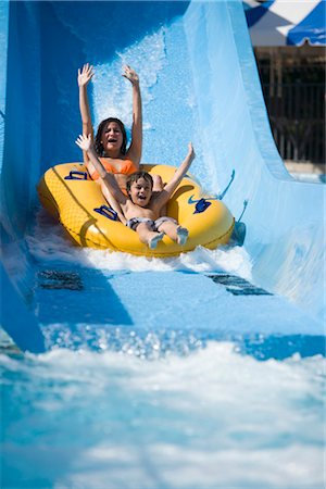 Portrait of mother and son sliding down water slide together on innertube in water park Stock Photo - Rights-Managed, Code: 842-02653786
