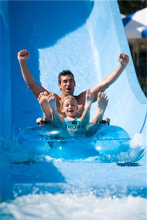 Portrait of father and daughter sliding down water slide together on innertube in water park Stock Photo - Rights-Managed, Code: 842-02653787