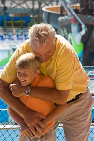Father and son hugging and wrestling with water park in background Stock Photo - Rights-Managed, Code: 842-02653911