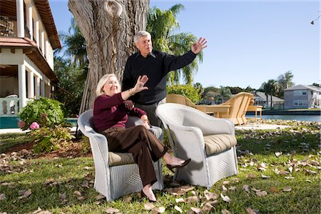Portrait of senior couple waving in yard of luxurious home Stock Photo - Rights-Managed, Code: 842-02754433