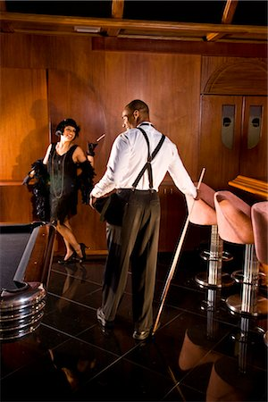Rear view of African American man with woman in flapper dress standing in 1920s bar Stock Photo - Rights-Managed, Code: 842-02754548