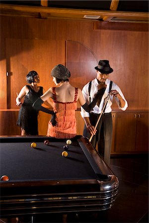 Portrait of African American man playing billiards as woman in flapper dress touches him Stock Photo - Rights-Managed, Code: 842-02754563