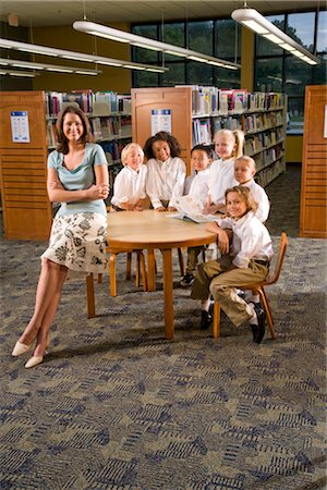 Portrait of elementary school teacher and pupils sitting at table in library Stock Photo - Rights-Managed, Code: 842-02751776