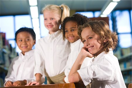 Four elementary school children smiling in library Stock Photo - Rights-Managed, Code: 842-02751869
