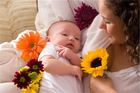 Close-up of mother holding 3 month year old baby in arms with flowers Stock Photo - Rights-Managed, Code: 842-02751977