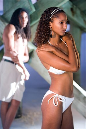 Young Jamaican man leaning on beach pier checking out woman in bikini Stock Photo - Rights-Managed, Code: 842-02752273