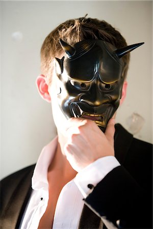 Portrait of young man in tuxedo holding masquerade mask Stock Photo - Rights-Managed, Code: 842-02752372