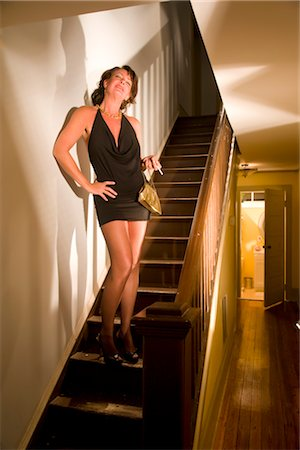 Portrait of sexy hooker with cigarette standing on stairs in house Stock Photo - Rights-Managed, Code: 842-02753059