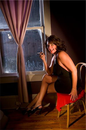 Portrait of sexy hooker with cigarette sitting in chair at house Stock Photo - Rights-Managed, Code: 842-02753053