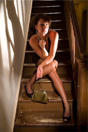Portrait of hooker lighting cigarette while sitting on stairs in house Stock Photo - Rights-Managed, Code: 842-02753066