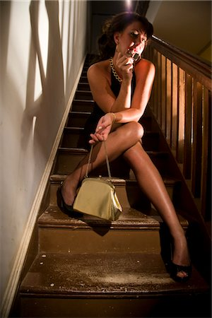 Portrait of hooker smoking cigarette on stairs in house Stock Photo - Rights-Managed, Code: 842-02753067