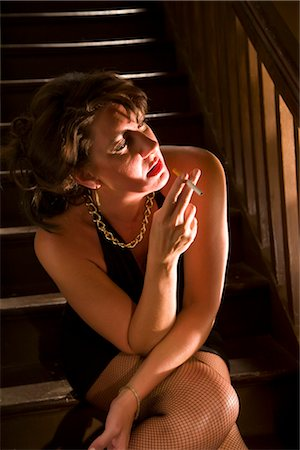 Hooker smoking cigarette sitting on stairs in house Stock Photo - Rights-Managed, Code: 842-02753068
