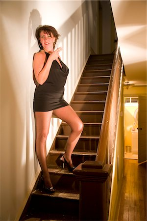 Portrait of sexy hooker with cigarette standing on stairs in house Stock Photo - Rights-Managed, Code: 842-02753060