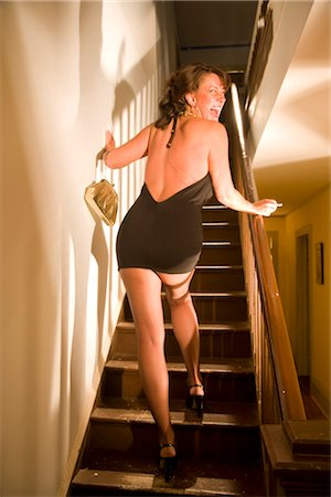 Rear view of hooker walking up stairs in house and laughing Stock Photo - Rights-Managed, Code: 842-02753062